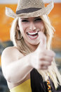 Vivacious laughing woman giving a thumbs up beautiful young wearing trendy straw hat gesture of approval with focus to her face Stock Photography