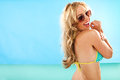 Vivacious long haired blond woman in a bikini glancing back over her shoulder at the camera as she stands facing out to sea Royalty Free Stock Photography