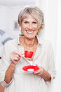 Vivacious older woman drinking espresso coffee modern from a small red cup standing indoors smiling at the viewer Royalty Free Stock Image