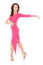 Vivacious woman dancing in a sexy pink dress beautiful balancing on one foot her high heels with her arms outspread on white Royalty Free Stock Images