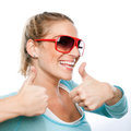 Vivacious woman giving a thumbs up enthusiastic blond wearing sunglasses of approval with beaming smile isolated studio portrait Stock Image
