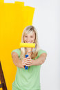 Vivacious woman painting with yellow paint holding up a roller in front of her a pleased satisfied smile Royalty Free Stock Image