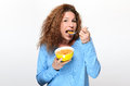 Vivacious young woman eating breakfast cereal Royalty Free Stock Photo