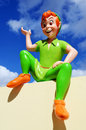 Vivid colored figure peter pan part huge private collection seen here sitting wall one his typical poses blue sky background Royalty Free Stock Photos