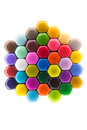 Vivid hexagonal pattern in rainbow colours the of the created by the tightly packed backs of coloured pencil crayons isolated on Royalty Free Stock Photo
