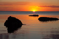 Vivid orange sunset over water, with rock silhouettes Royalty Free Stock Photo