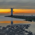Vivid sunrise over pier and lighthouse in swinoujscie poland Stock Photography