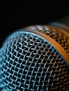 Vocal microphone macro over dark background photo of a in low light lit with stage lights Royalty Free Stock Photos