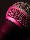 Vocal microphone in pink light macro photo of a lit with stage lights Stock Image