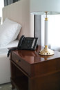 Voip phone in hotel room personal near the bed Royalty Free Stock Photo