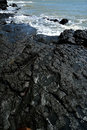 Volcanic rock rocks on beach beside sea with black color and featured texture Stock Photos