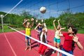 Volleyball game among children who actively play with the ball on the playground during summer sunny day Stock Photos
