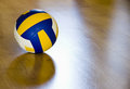 Volleyball on hardwood floor Royalty Free Stock Photo