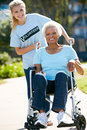 Volunteer Pushing Senior Woman In Wheelchair Stock Photos