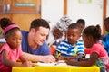Volunteer teacher sitting with preschool kids in a classroom Stock Images