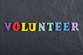 VOLUNTEER word on black board background composed from colorful abc alphabet block wooden letters, copy space for ad Royalty Free Stock Photo
