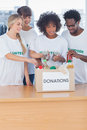 Volunteers putting food in donation box their office Royalty Free Stock Photos