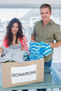 Volunteers taking out clothes from a donation box for charity Royalty Free Stock Images