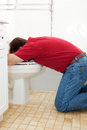 Vomiting in the toilet man bathroom into Stock Photography