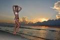 Vorbildliche aufstellung des schönen brunette auf der ozeanküste bei sonnenaufgang Stockfoto