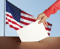 Vote female hand with ballot and box on flag of usa Royalty Free Stock Image