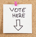 Vote here post on wooden background Royalty Free Stock Images