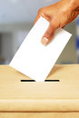 Voting on election day democracy concept african american putting blank ballot in box Stock Image