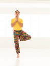 Vrksasana pose colorful dressed male repeating yoga exercises in a white room with window background Royalty Free Stock Photos