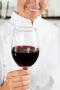 Vrouwelijke chef kok holding wine glass Stock Afbeelding