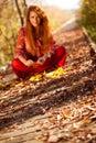 Vrouwenzitting in autumn nature uit nadruk Stock Foto's