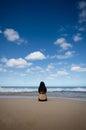 Vrouwenzitting op sandy beach looking naar horiz Royalty-vrije Stock Foto