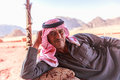 Wadi Rum, Jordan – June 20, 2017: Bedouin man or Arab man in traditional outfit, lying down on the couch, desert background.