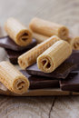 Wafer rolls with pieces of chocolate on a wooden rustic table Stock Images