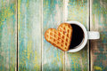 Waffle biscuits in shape of heart with cup of coffee on wooden background for Valentines day Royalty Free Stock Photo