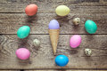 Waffle cone with Easter eggs on old wooden background. Space for