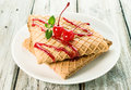 Waffles with cherry topping on a wooden background Royalty Free Stock Images