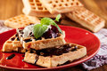 Waffles with chocolate sauce whipped cream and confiture on plate Stock Images