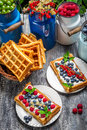 Waffles with fresh collected berry fruit on old wooden table Royalty Free Stock Photos