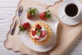 Waffles with fresh strawberries and coffee closeup. horizontal t Royalty Free Stock Photo