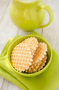 Waffles in the green bowl with jug of milk ceramic on old retro kitchen table Royalty Free Stock Image