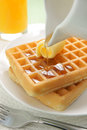 Waffles and maple syrup pouring on a stack of Stock Images