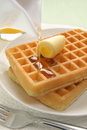 Waffles and maple syrup pouring on a stack of Royalty Free Stock Photography