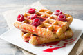 Waffles with raspberries on a wood table and ingredients Royalty Free Stock Image