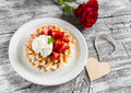 Waffles with strawberries and vanilla ice cream red rose and paper heart on a light wooden background Stock Images