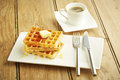 Waffles with syrup on white dish and wooden table top Stock Photo