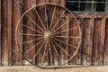 Wagon wheel background an old rusty leaning on a barn wall Royalty Free Stock Photography