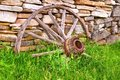Wagon wheel broken leans against a century old stone wall fayette state park garden michigan Royalty Free Stock Image