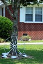 Wagon wheel a metal laying against a tree in a yard painted white Royalty Free Stock Photography