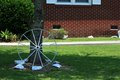Wagon wheel a metal laying against a tree in a yard painted white Royalty Free Stock Photos