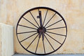 Wagon wheel old metal leaning against a rustic painted wall Royalty Free Stock Images